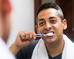A man with dental implants in Vero Beach brushing