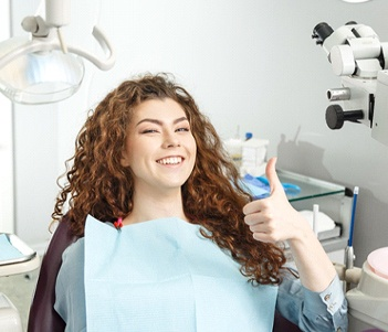 Woman smiling in dental chair with thumb up
