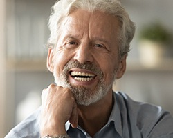 An older man wearing a button-down shirt and smiling after receiving his dental implants