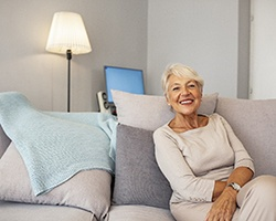 An older woman seated on a couch and showing off her new and improved smile