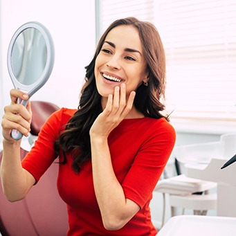 Woman admiring results of tooth recontouring in mirror