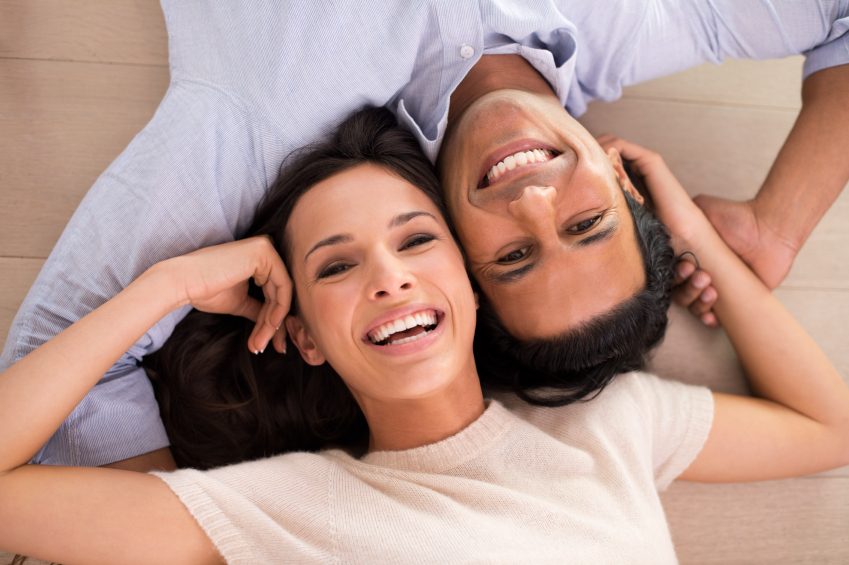 Ahusband and wife lying together on a wooden floor
