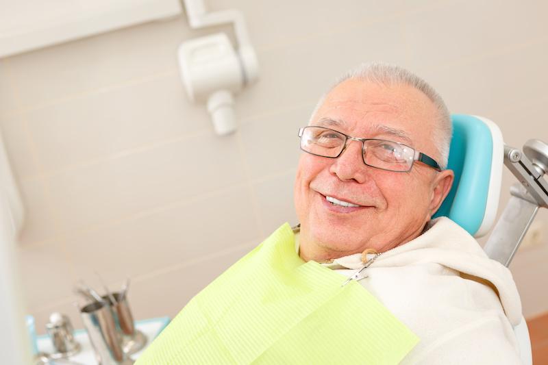 senior man smiling in dental chair