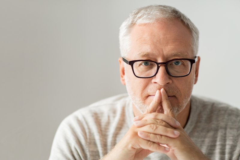 An older man covering his mouth.
