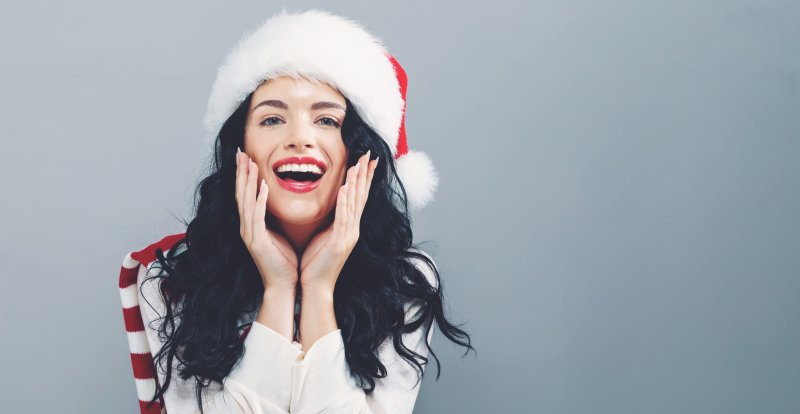 a young woman smiling while wearing a Santa hat