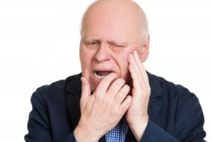 Pained man with hand on cheek has damaged dentures
