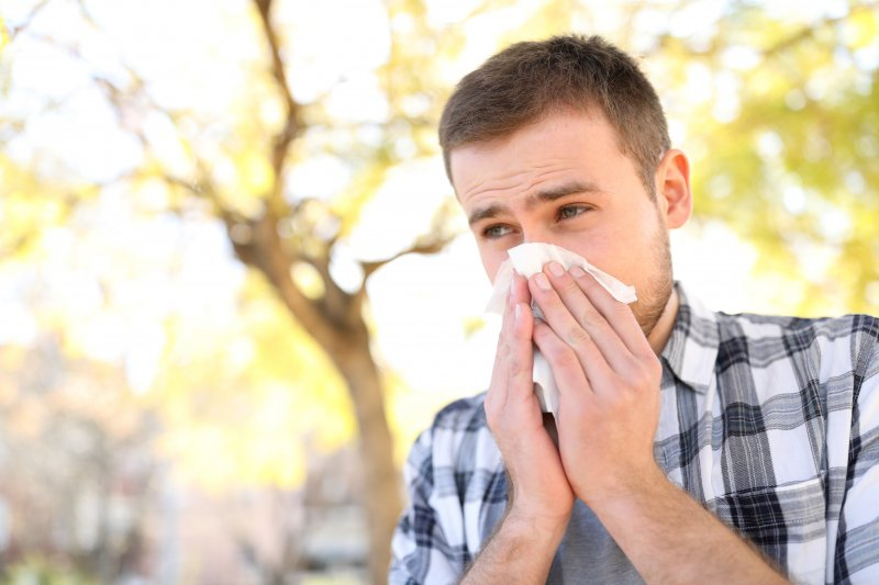 a man wearing a gray plaid shirt uses a tissue to blow his nose